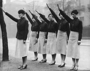 Women 'black-shirts'  from Sir Oswald Mosley's British Union of Fascists on parade in Liverpool give the fascist salute. Their uniform is a black shirt and tie, beret and slightly flared skirts. All are wearing high heel shoes of various styles.   (Photo by Fox Photos/Getty Images)
